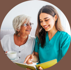 caregiver reading a book for her patient