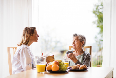 caregiver talking to senior woman with healthy foods in the table