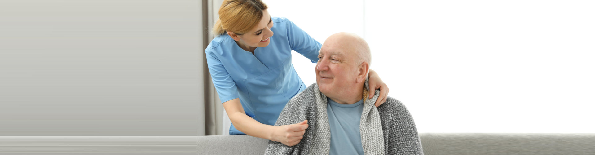 caregiver giving clothes to her patient